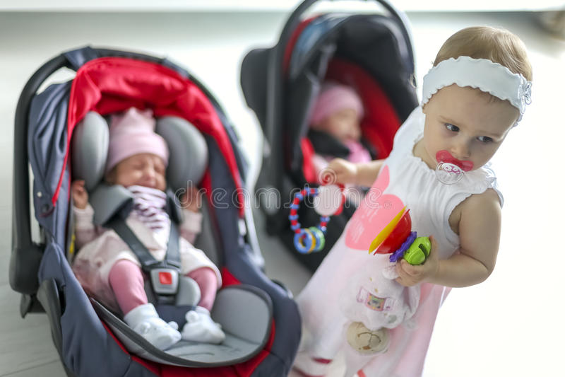 De pasgeboren baby brengt meisjeszitting in een autozetel samen stock afbeeldingen