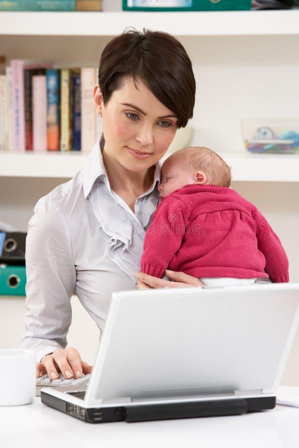 De Pasgeboren Baby die van WomanWith van Huis werkt stock afbeelding