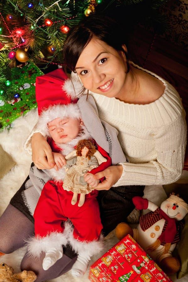 De pasgeboren baby in Kerstmankleren die op een moeder slapen overhandigt stock foto's