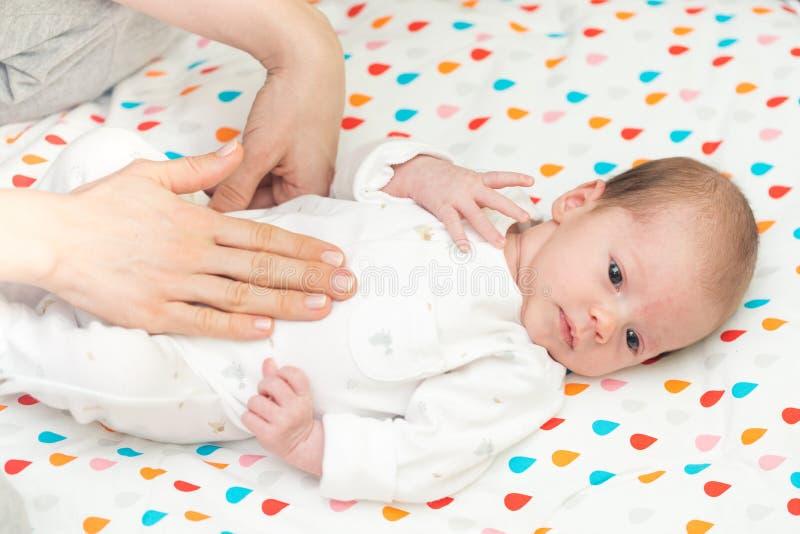 De pasgeboren baby kleedde zich in wit terug leggend op haar royalty-vrije stock fotografie