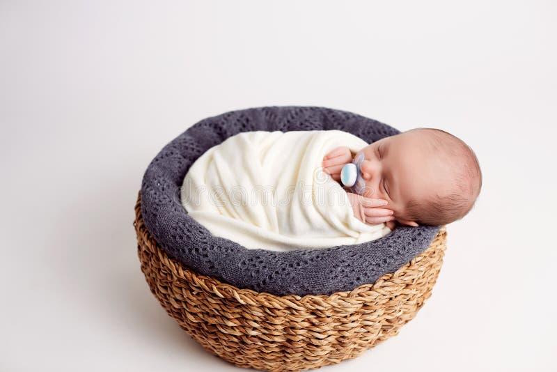 De pasgeboren babyjongen, die vreedzaam in mand slapen, kleedde zich in gebreide, gelukkig en leuke uitrusting, die uit koelen royalty-vrije stock afbeelding
