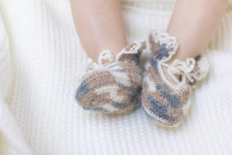 De pasgeboren babyvoeten sluiten omhoog in buiten van wol de bruine gebreide sokken op een witte deken De baby is in de voederbak royalty-vrije stock foto
