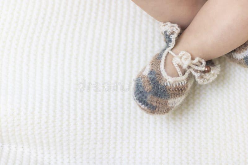 De pasgeboren babyvoeten sluiten omhoog in buiten van wol de bruine gebreide sokken op een witte deken De baby is in de voederbak royalty-vrije stock fotografie