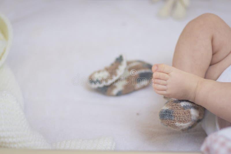 De pasgeboren babyvoeten sluiten omhoog in wolsokken op een witte deken De baby is in de voederbak ??n sok wordt verwijderd uit d stock fotografie