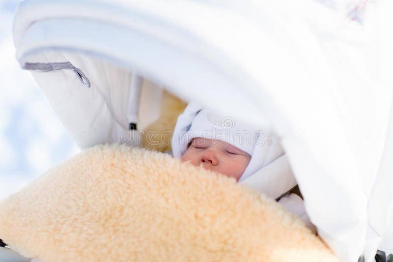 De pasgeboren slaap van de babyjongen in wandelwagen in de winter stock foto's
