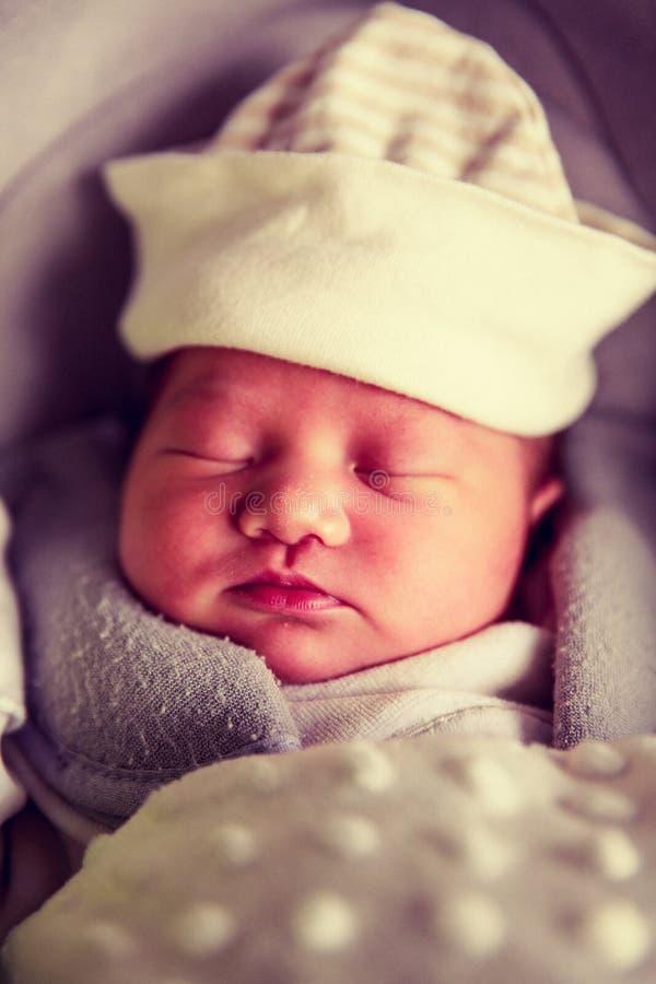 De pasgeboren slaap van het babymeisje in de autozetel stock fotografie