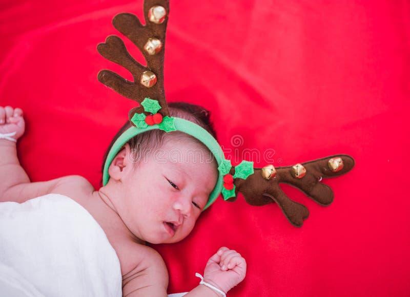 De pasgeboren slaap van het babymeisje met herten stock afbeelding