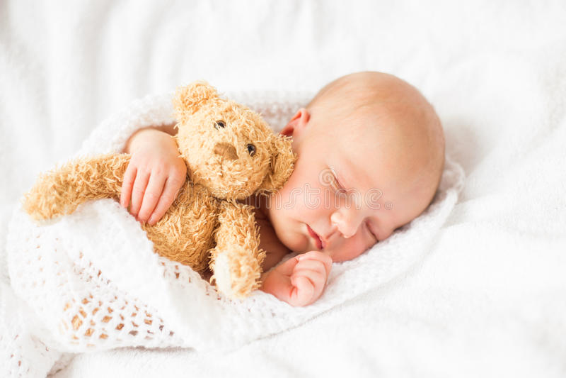 De pasgeboren slaap van het babymeisje met teddybeer stock afbeeldingen