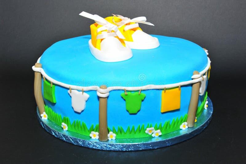 De pasgeboren van babyschoenen en kleren cake van het themafondantje stock afbeelding