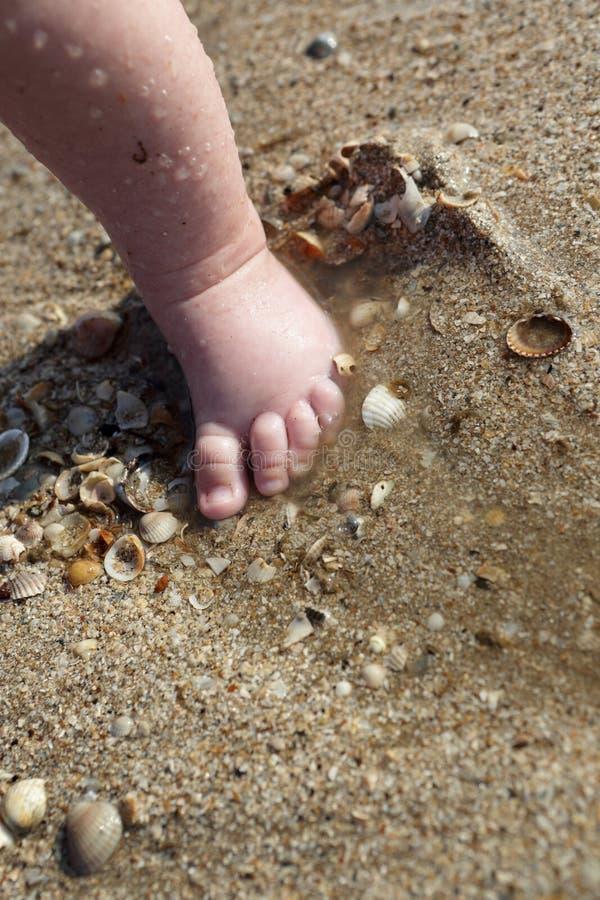 De pasgeboren voet van de babyjongen in het zand stock afbeeldingen