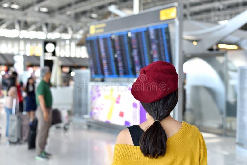 De passagier die vluchtstatus controleren bij de vertoning van de luchthaveninformatie, Aziatische reiziger vertrek bekijken en a stock foto's