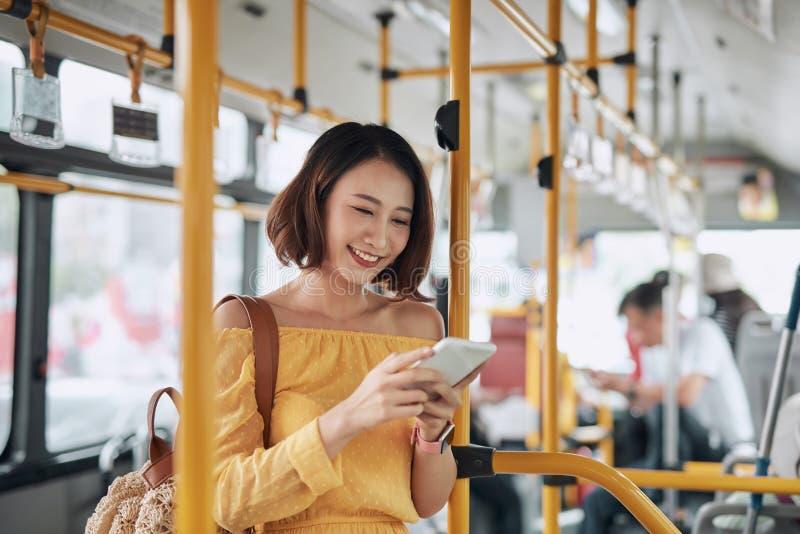 De passagier gebruikt smartphone in de bus of de trein, de technologische levensstijl, het vervoer en het reisconcept stock afbeelding