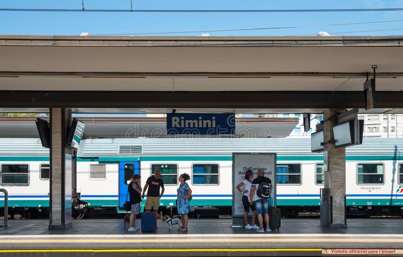 De passagiers die per spoor reizen wachten op een trein op het platform van de toevluchtstad van Rimini royalty-vrije stock foto's