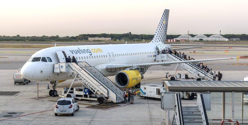 De passagiers schepen op een vliegtuig in stock foto