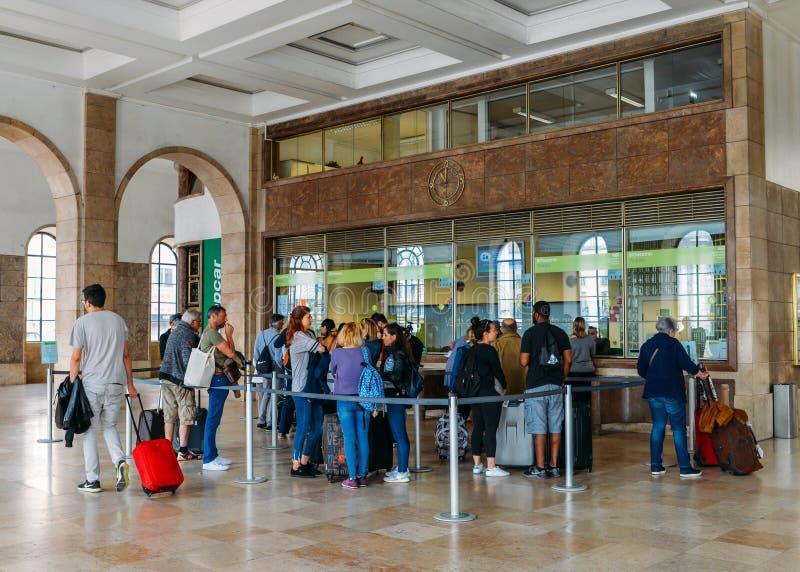 De passagiers vormen een rij om kaartjes bij het station die van Lissabon te kopen ` s Santa Apolonia de interlokale trein van Po royalty-vrije stock foto's