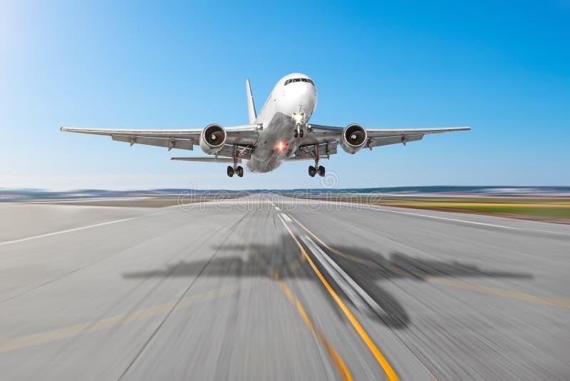 De passagiersvliegtuigen met een gietvorm stellen op het asfalt in de schaduw die op een baanluchthaven landen, motieonduidelijk  royalty-vrije stock foto's
