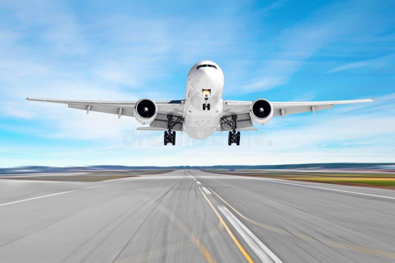 De passagiersvliegtuigen met een gietvorm stellen op het asfalt in de schaduw die op een baanluchthaven landen, motieonduidelijk  royalty-vrije stock fotografie