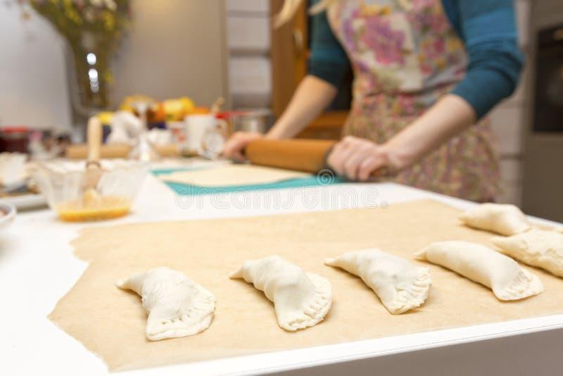 De pastei van het vrouwenbaksel in haar huiskeuken stock foto