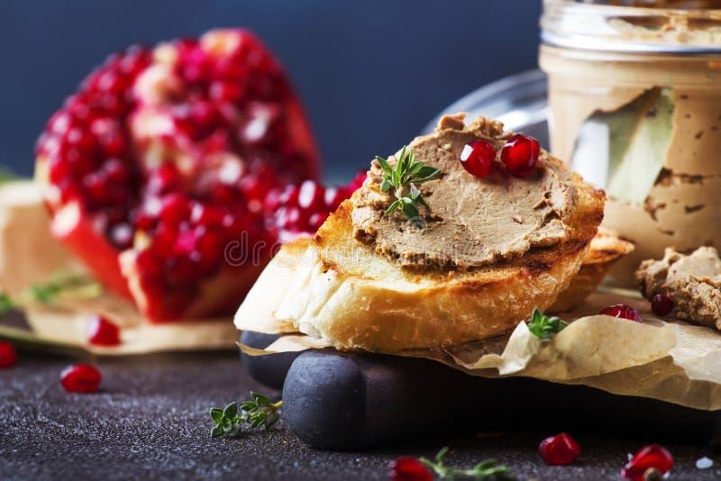 De pastei van de vleeslever op geroosterd brood met fruitzaden en kruidkruid, bruine keukenlijst, kopieert ruimte, selectieve nad royalty-vrije stock afbeeldingen