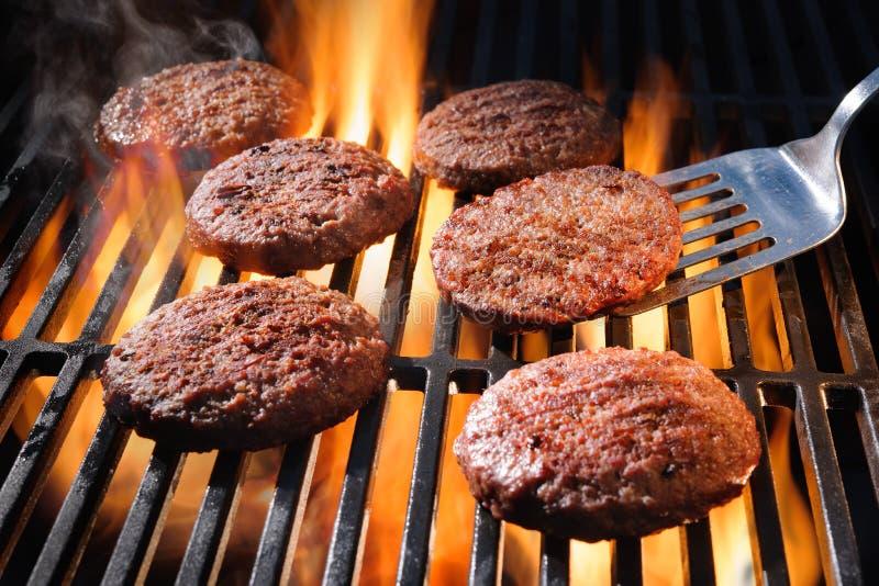 De pasteitjes die van de rundvleeshamburger op de barbecue sissen stock foto