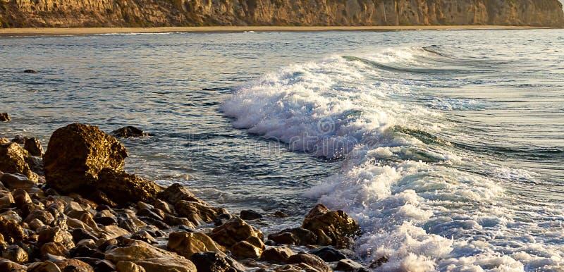 De pastelkleur kleurde schuim die voor golf naar rotsachtige kust met klip en zandig strand rollen royalty-vrije stock afbeelding