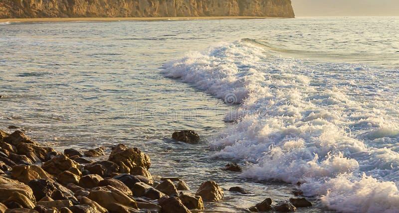 De pastelkleur kleurde schuim die voor golf naar rotsachtige kust met klip en zandig strand rollen stock foto