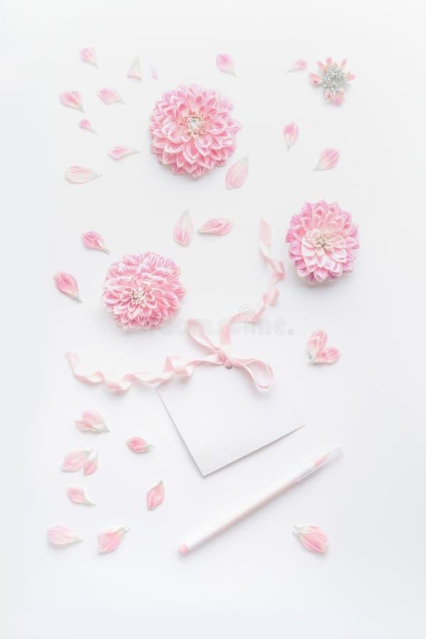 De pastelkleurspot omhoog met roze bloemen en bloemblaadjes, lege document kaart met lint en puntpen op witte Desktopachtergrond, royalty-vrije stock foto's
