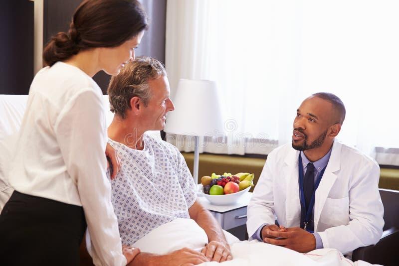 De Patiënt en de Vrouw van artsentalking to male in het Ziekenhuisbed royalty-vrije stock foto's