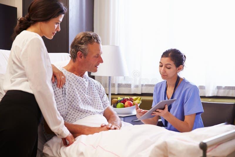 De Patiënt en de Vrouw van verpleegsterstalking to male in het Ziekenhuisbed stock afbeelding