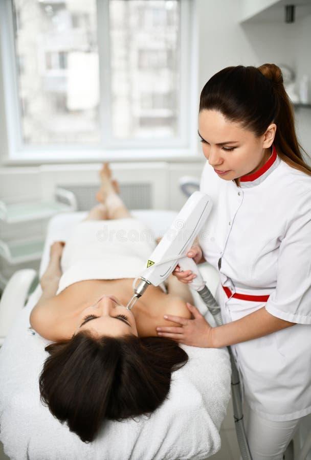 De patiënt ligt op de laag terwijl de arts een kosmetische procedure aangaande haar gezicht met medische apparatuur uitvoert In e royalty-vrije stock foto