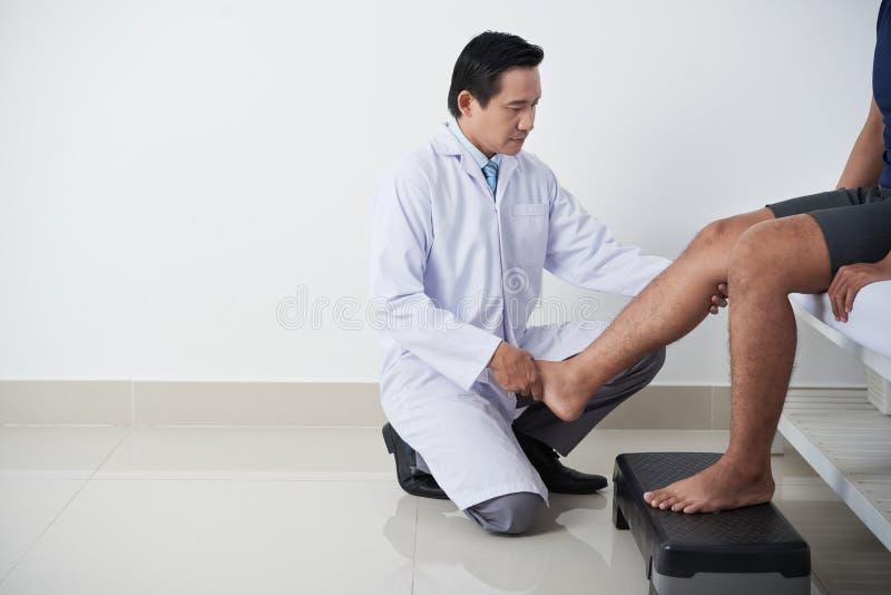 De Patiënt van artsenexamining leg of stock afbeelding