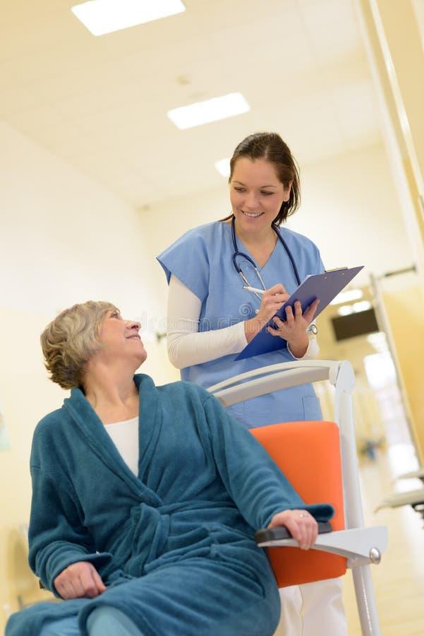 De patiënt van het verpleegstershorloge in het ziekenhuis stock afbeeldingen