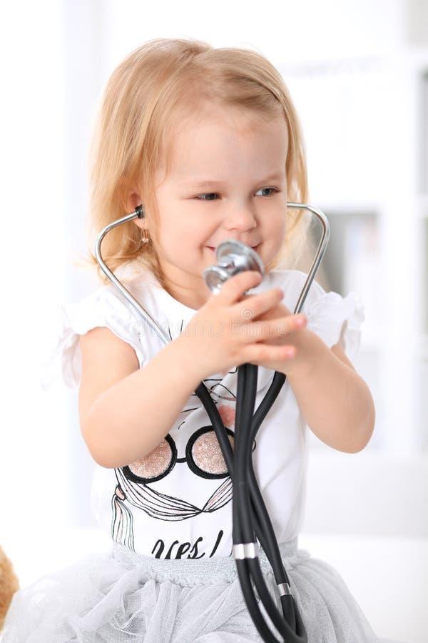 De pediater behandelt baby in het ziekenhuis Het meisje is onderzoekt door arts met stethoscoop Vertragingen en wapens stock foto