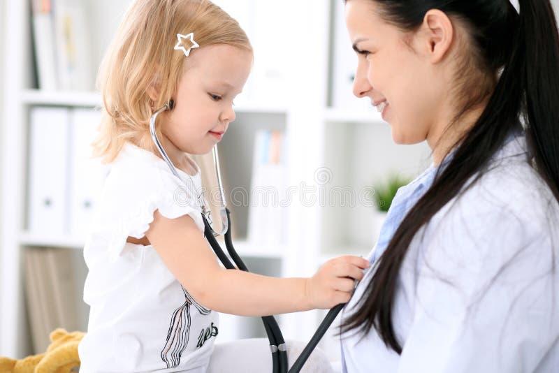 De pediater behandelt baby in het ziekenhuis Het meisje is onderzoekt door arts met stethoscoop Vertragingen en wapens stock fotografie