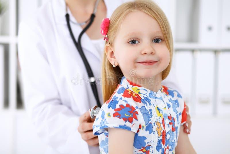 De pediater behandelt baby in het ziekenhuis Het meisje is onderzoekt door arts door stethoscoop Vertragingen en wapens royalty-vrije stock afbeeldingen