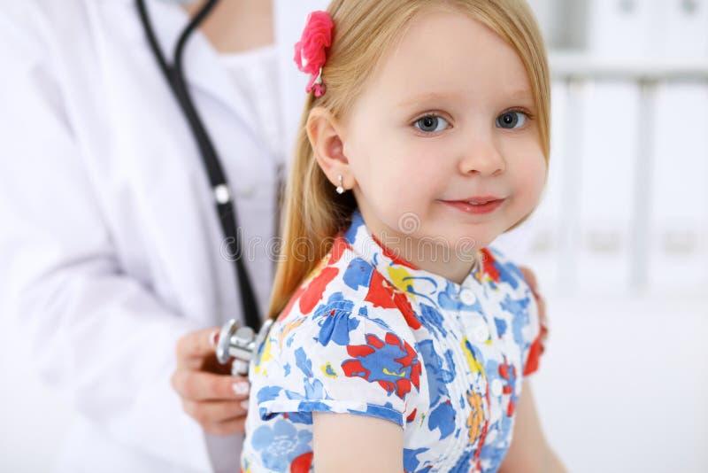 De pediater behandelt baby in het ziekenhuis Het meisje is onderzoekt door arts door stethoscoop Vertragingen en wapens stock foto's