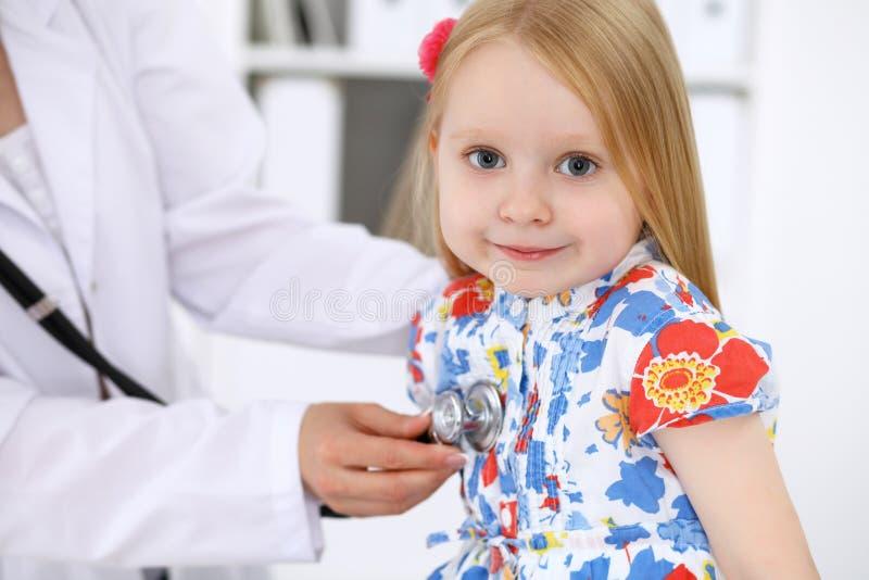 De pediater behandelt baby in het ziekenhuis Het meisje is onderzoekt door arts door stethoscoop Vertragingen en wapens stock afbeeldingen