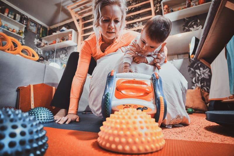De pediater doet speciale ortophedic oefeningen voor weinig leuke peuter stock foto's