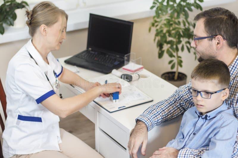 De pediater stempelt een voorschrift voor geneesmiddelen voor een kind De papa zit op een stoel en houdt zijn zoon op zijn knieën stock fotografie