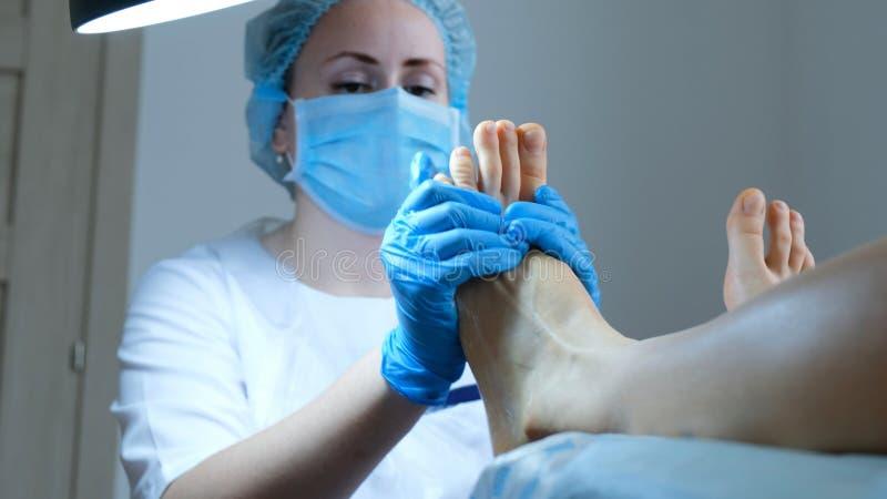 De pedicuremeester maakt een oude laag van huid met een rasp van de voetpedicure schoon en bevochtigt de voeten met gel stock foto's