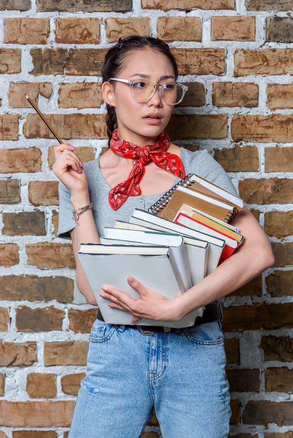 De peinzende Aziatische boeken en het potlood van de studentenholding royalty-vrije stock fotografie