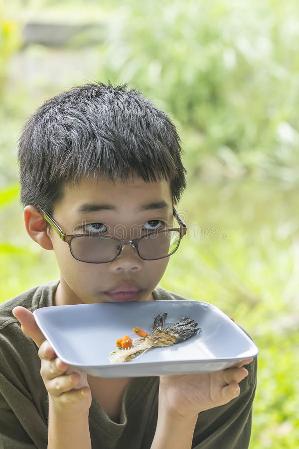De peinzende die jongen bekijkt visgraat duidelijk op plaat wordt gegeten royalty-vrije stock foto's