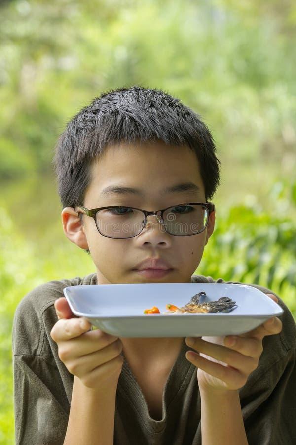 De peinzende die jongen bekijkt visgraat duidelijk op plaat wordt gegeten stock foto's