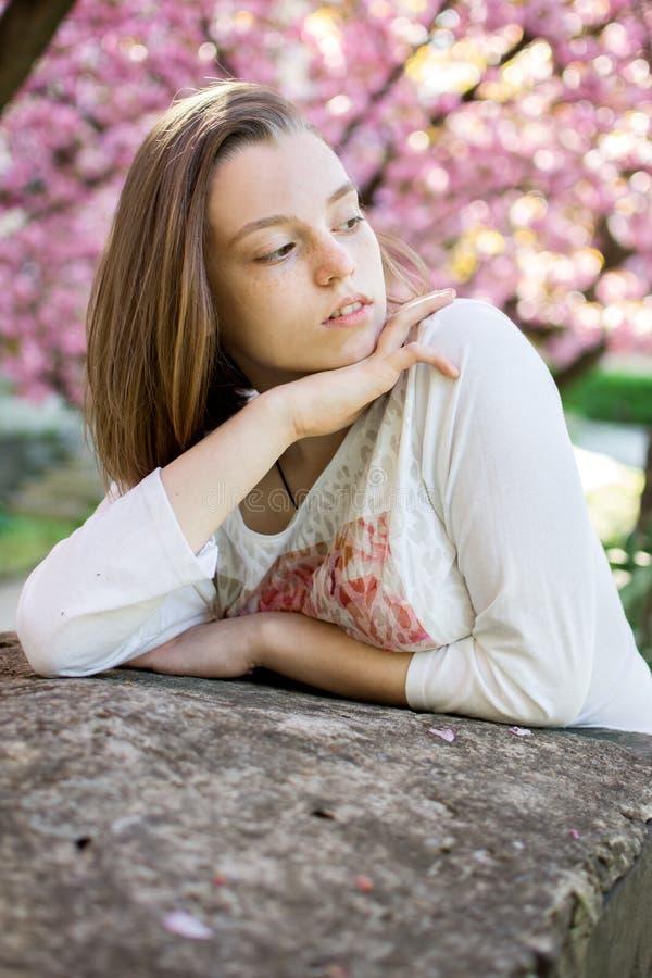 De peinzende en droevige zitting van het tienermeisje op een achtergrond van het bloeien royalty-vrije stock afbeelding