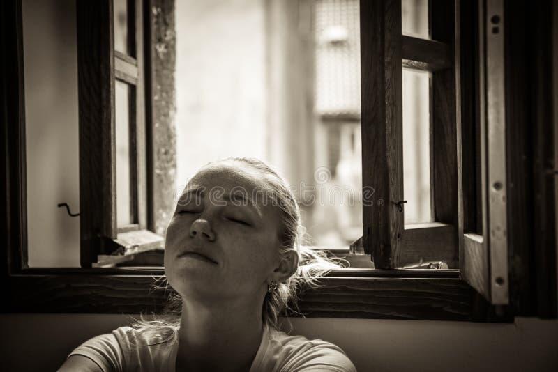 De peinzende jonge vrouw met gesloten ogen verloor in gedachten die en dichtbij geopend venster in zwart-witte kleur in vintag on stock afbeelding