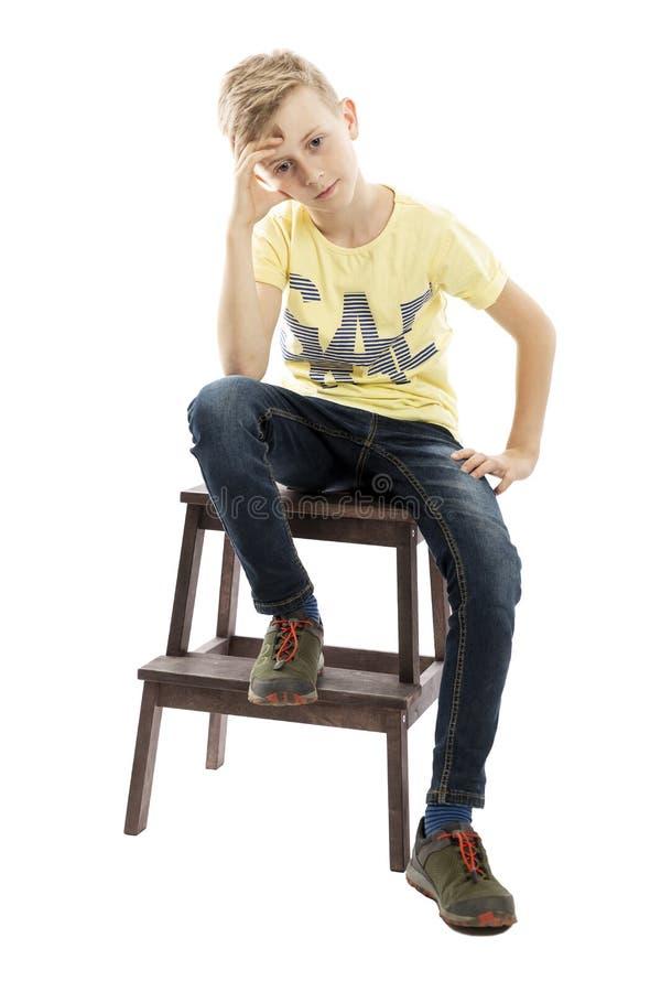 De peinzende kereltiener in jeans en een gele T-shirt zit op een stoel Over witte achtergrond royalty-vrije stock fotografie