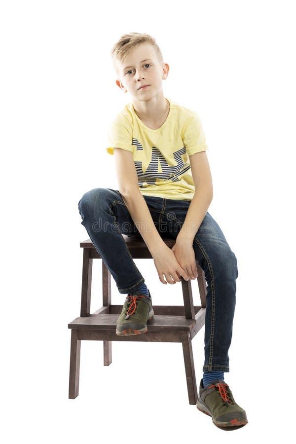 De peinzende kereltiener in jeans en een gele T-shirt zit op een stoel Over witte achtergrond royalty-vrije stock foto's