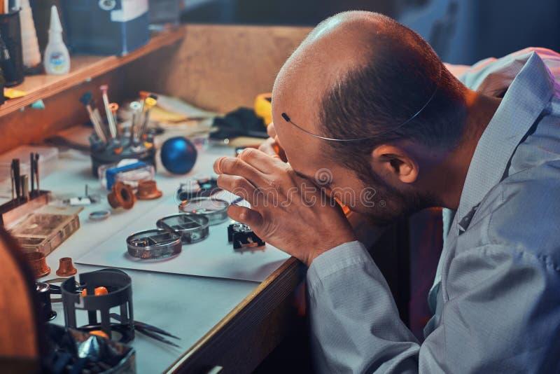 De peinzende meester werkt aan het horloge van de cliënt op zijn workshop stock afbeelding