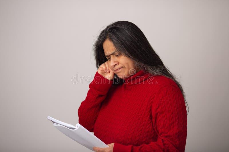 De peinzende Spaanse Vrouw bekijkt Nota's stock afbeeldingen