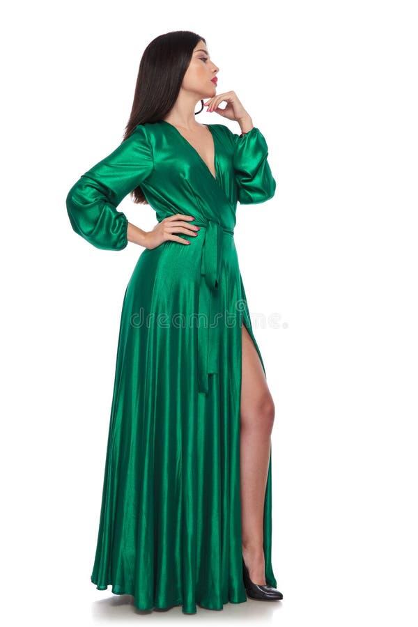De peinzende vrouw die een groene balzaalkleding dragen kijkt aan kant royalty-vrije stock foto